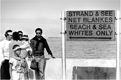 """Sebuah tanda di pantai Afrika Selatan dari periode Apartheid, membatasi penggunaannya hanya untuk kulit """"putih"""". Orang- orang berkulit lebih cerah memang lebih rentan terhadap bahaya sengatan Matahari ketimbang orang berkulit gelap. Meskipun demikian, tidak ada logika biologi di balik pembedaan pantai- pantai di Afrika Selatan. Pantai-pantai yang dikhususkan bagi orang berkulit cerah tak memiliki ciri tingkat radiasi ultraviolet lebih rendah."""